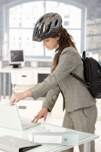 8251378-Young-attractive-businesswoman-leaving-office-by-bike-shutting-down-her-laptop-wearing-helmet-and-ba-Stock-Photo